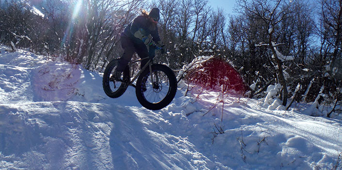 Fat biker catching air in the snow