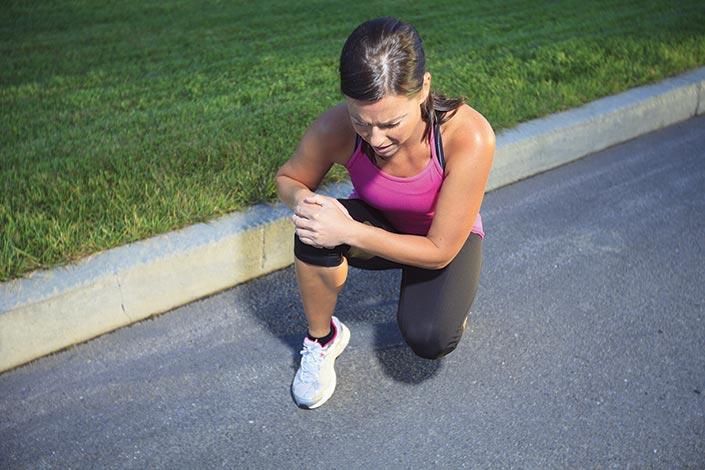 female runner holding an injured knee