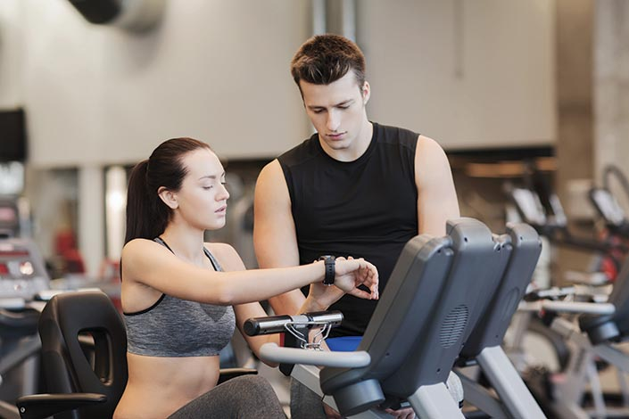 Guy and Girl checking a heart rate watch in the gym