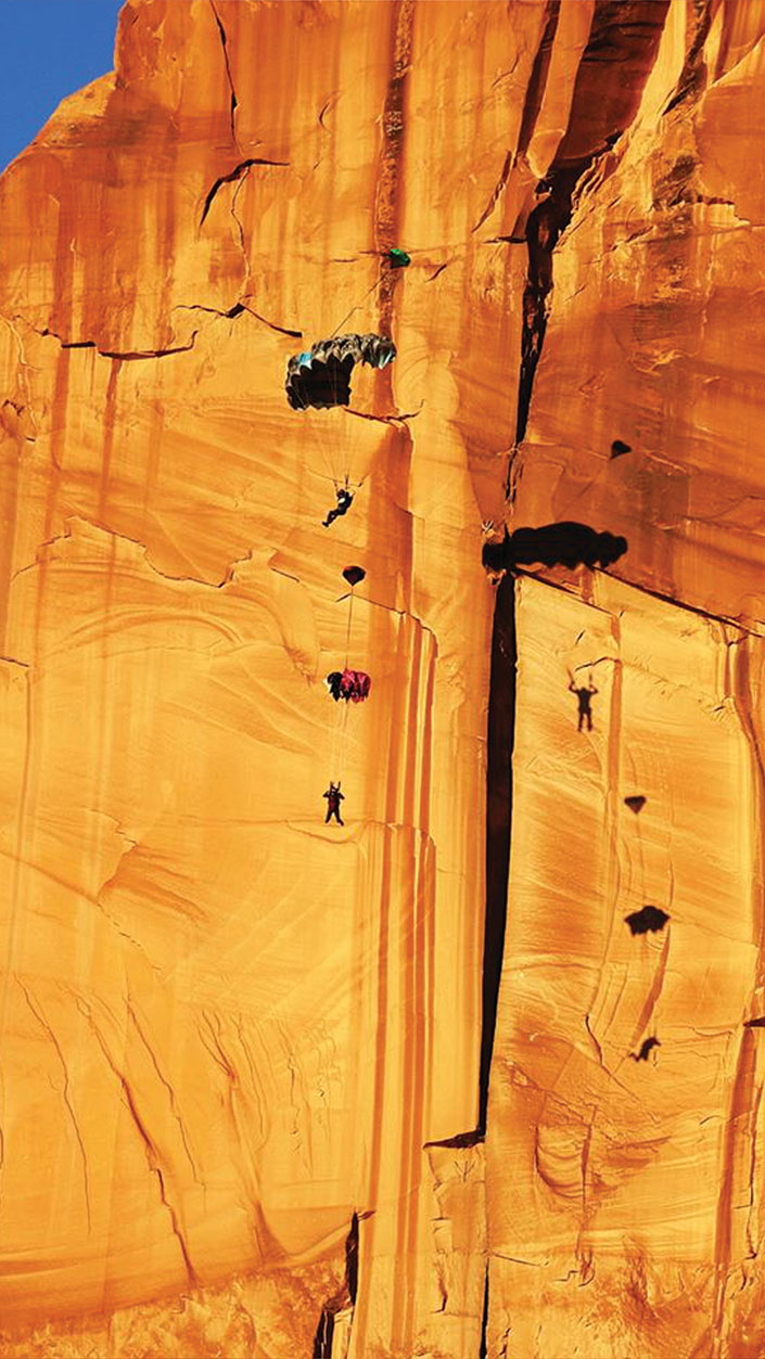 Two BASE jumpers parachuting along a red rock cliff in Moab, Utah