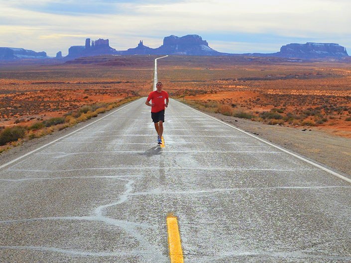 Cory Reese running on a desert road in monument valley