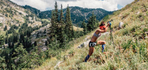 female trail runner running up mountain side