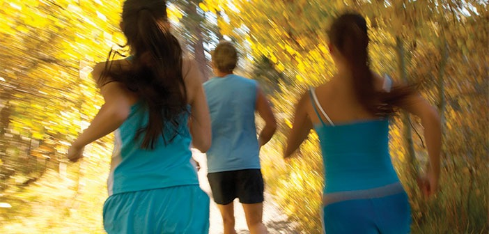 Two women and a man running in the Fall trees