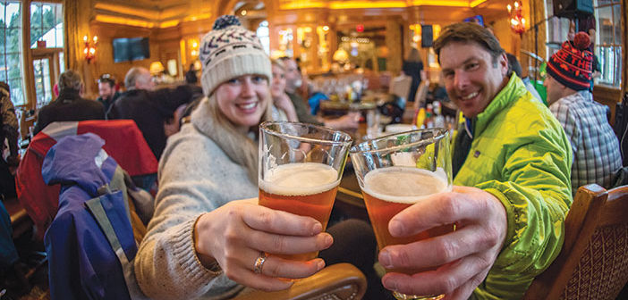A couple enjoying beers at an après ski lodge Cinnabar