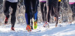 group of runners on a snowy trail