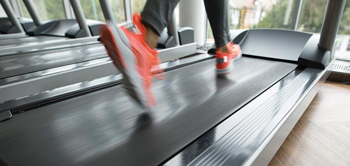 Runner on a treadmill with orange shoes