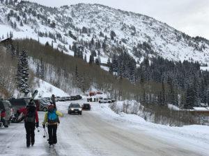 2 skiers walking in a parking lot