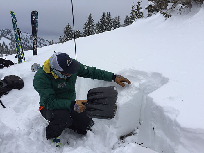 A man checking avalanche conditions with a shovel