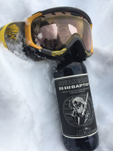 Epic Double Barrel beer bottle in the Snow with skiing goggles