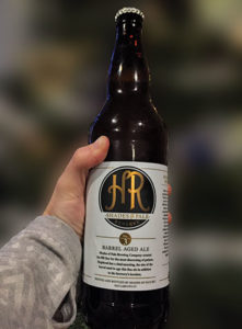 Hand holding a Shades of Pale Hogshead beer bottle