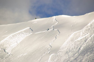 2 skiers on a mountain with an avalanche breaking