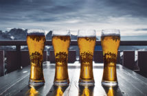 4 beers in glasses on a table with a winter mountain background