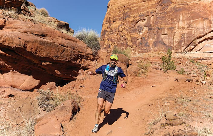 Man running on a red rock trail