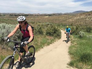 A woman and man biking on a trail in Boise Idaho