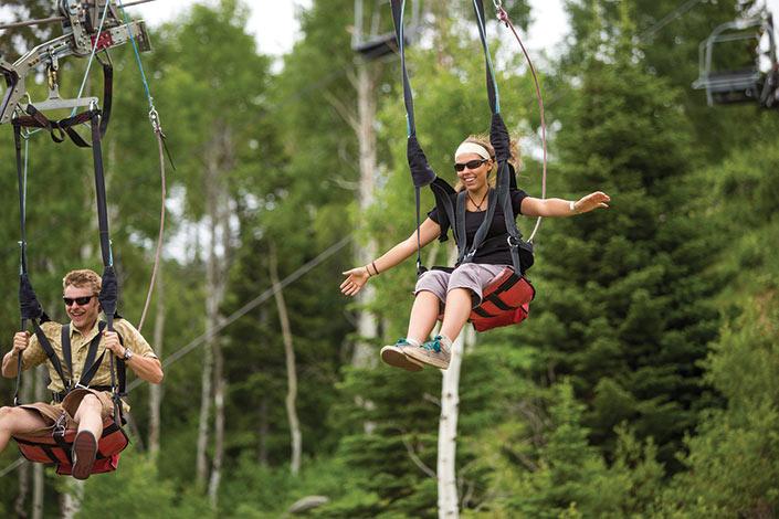 Man and woman ziplinning at park city resort