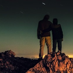 Man and woman standing atop a mountain at night