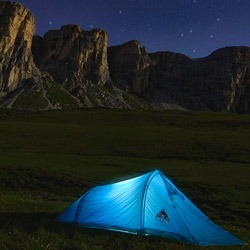 Tent glowing at night in wilderness
