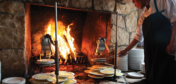 Cheese melting onto plates near fireplace