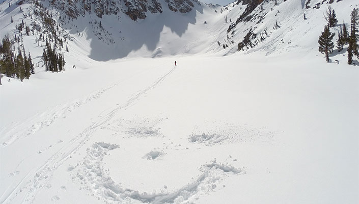Smiley face made in snow during backcountry hike