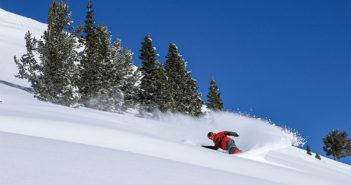 Snowboarding making a turn in powder