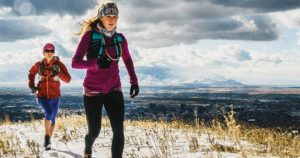 two women running in winter with Salt Lake City in the Background