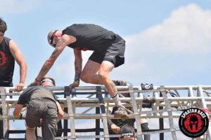 author Nick Como climbing an obstacle