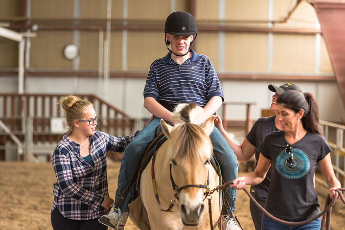 Volunteers helping man ride a horse