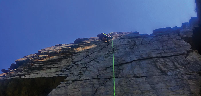 Looking up at a rock climber way up on a cliff face