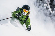 Skier in powder with green jacket and wearing a helmet