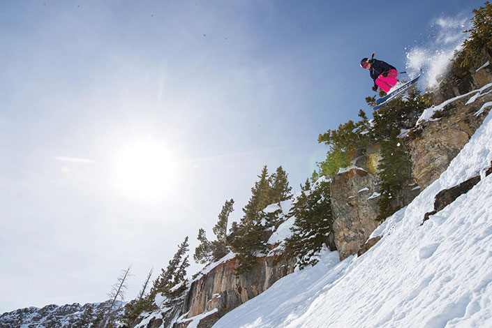Author Amy David skiing the Wasatch jumping off a cliff.