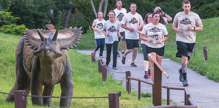 Runners on trail near a model triceratops