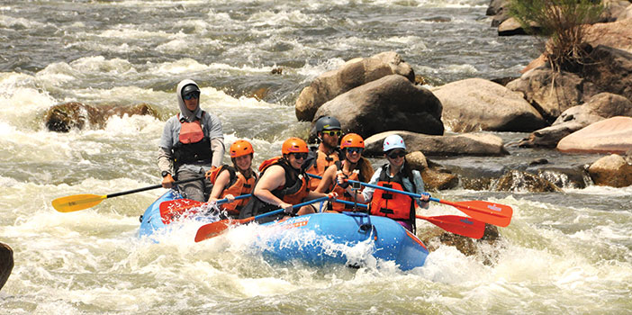 group in raft paddling through rapids on Arkansas River