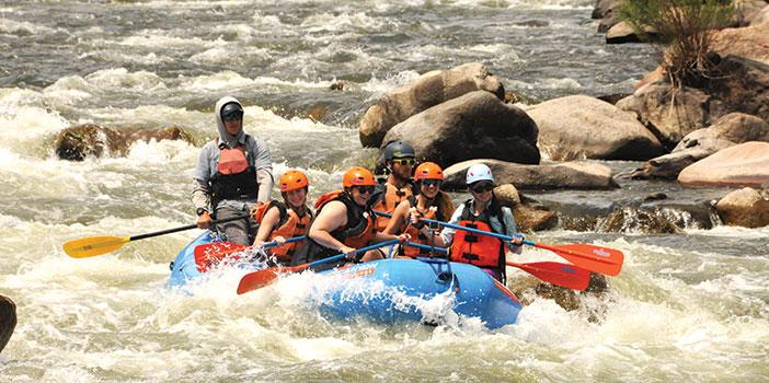 group in raft paddling through rapids on Arkansas River