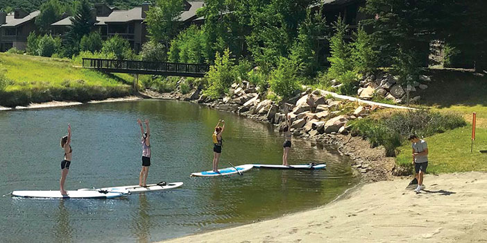 group doing yoga on stand up paddleboards on Deer Valley Pebble beach in park city