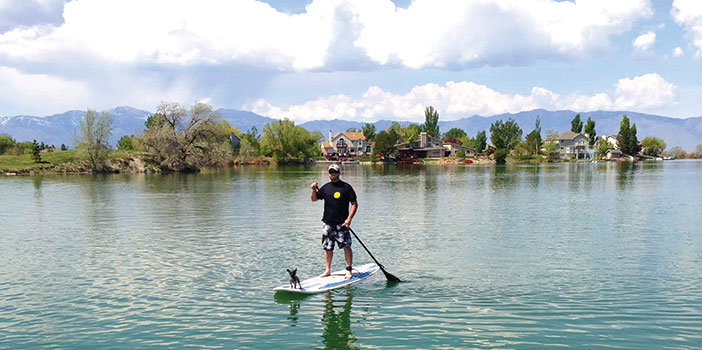 man with his dog on a stand up paddle board on Stansbury lake
