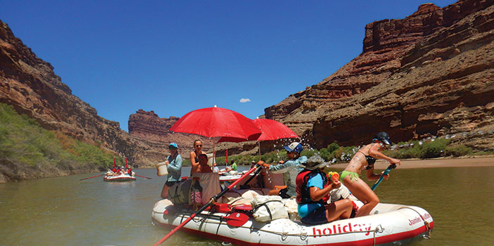 group having a water fight on a raft being rowed on Cataract Canyon