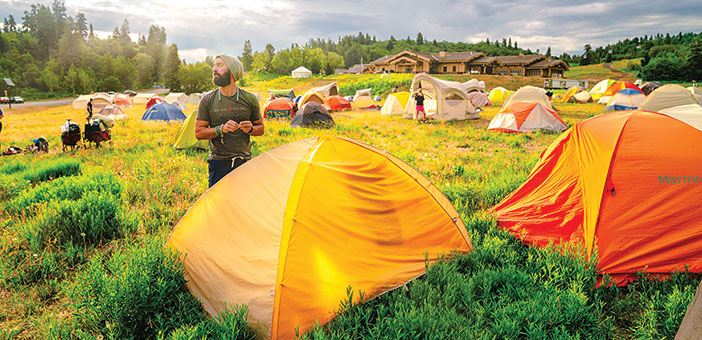 Man standing by a bunch of tents in a field