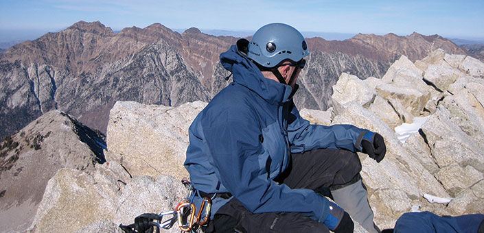 man in climbing gear at mountain peak in winter clothing